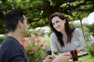 happy young loving couple having lunch at barbecue party outdoor in the garden